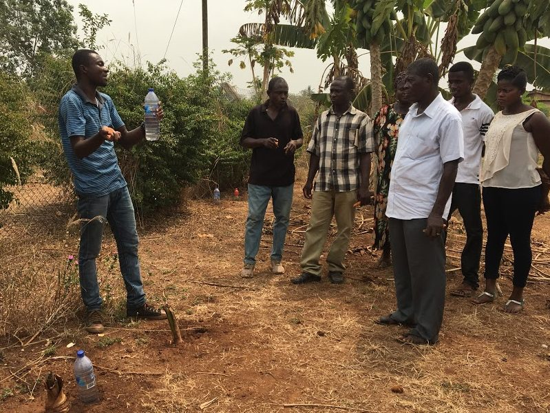 Training Center Manager Paul Simon holds a water bottle and discusses with farmers gathered around listening to him