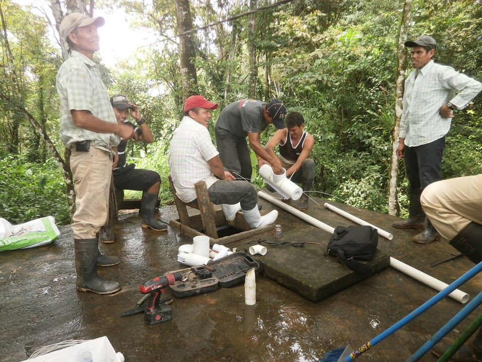 a group of men install a new water chlorination system