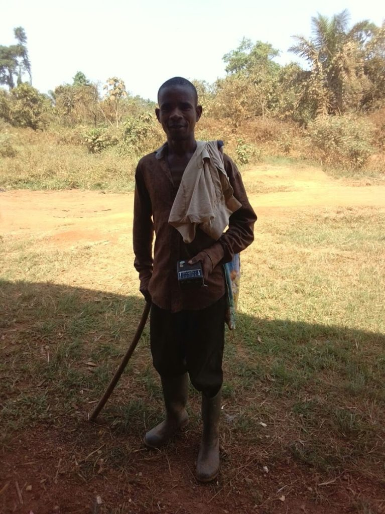 Abdullai man stands posing for picture in the shade