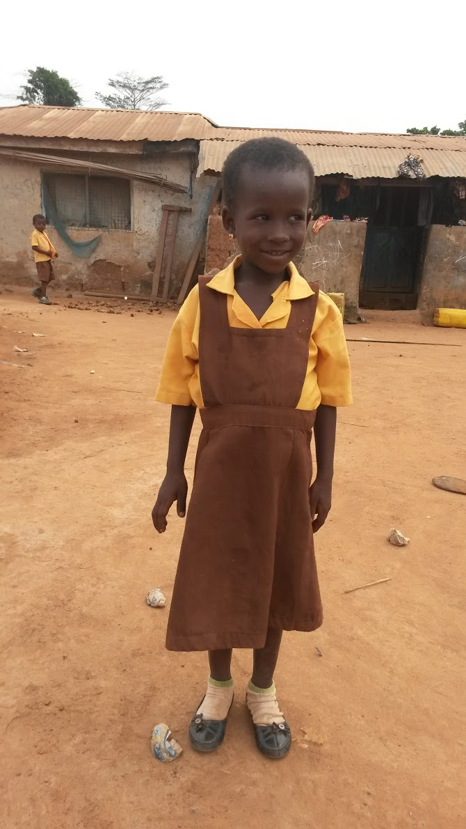 little girls in school uniform poses for picture